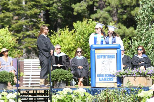 Jillian Ferre and Amelia Hurt present their teacher, Travis Halpern, as the honorary graduate.