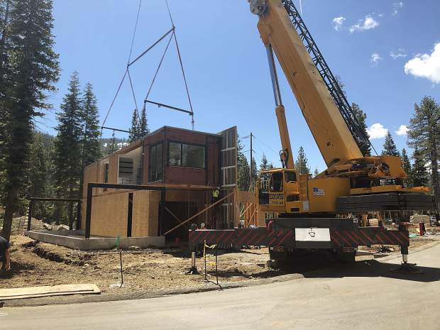 Six modules consisting of different living spaces like kitchens, bedrooms, and bathrooms, are assembled by workers to form two roughly 3,000-square-foot townhouses at the Palisades at Squaw Valley.