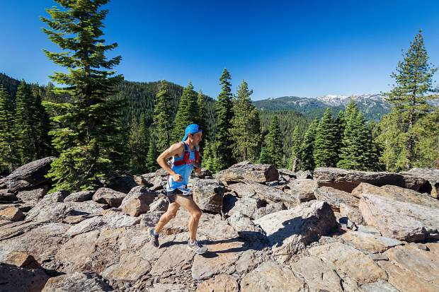 Race winner Jj Santana, of Las Vegas, runs far ahead of the pack on a rocky section of the new Big Chief Trail, roughly 19 miles from the start. Alpine Meadows and Squaw Valley are shown in the background. For more race photos, visit LefrakPhotography.com.