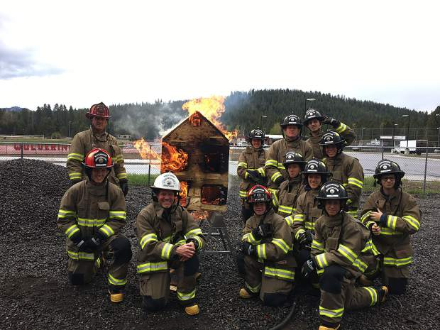 Students study fire behavior on a burning homes using a replicated doll house.