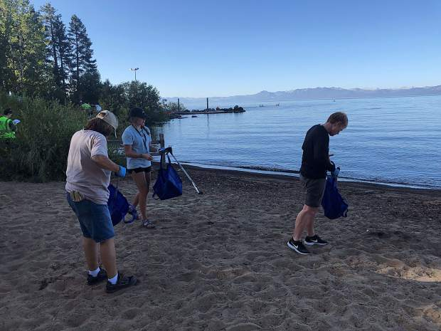 A trio of volunteers comb Kings Beach for trash on Monday, Sept. 2.