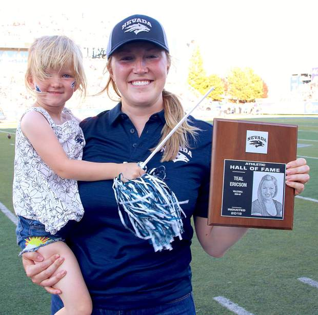 Former Nevada volleyball player Teal Ericson shows her Hall of Fame induction plaque while holding her daughter during halftime of the University of Nevada-Weber State football game.
