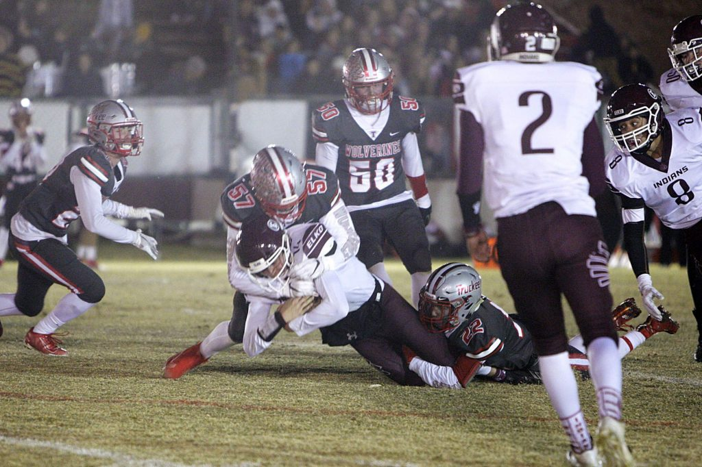 Junior Finn Loper (57) and Connor McMullen bring down an Elko ball carrier.