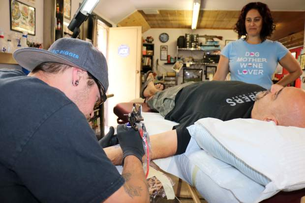 Scott Greenlaw, left, works on a tattoo on the wrist of Shawn Magurno, of Sparks, as his wife, Karina, looks on inside Lucky 7 Tattoo in Kings Beach.