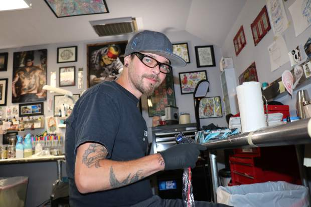 Scott Greenlaw gets his tattoo gun set up at his station inside Lucky 7 Tattoo in Kings Beach.
