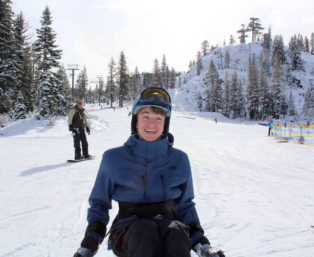 Myles Molnar, of Pleasanton, Calif., flashes a big smile while skiing down a run at Alpine Meadows with Achieve Tahoe. Molnar, 17, was paralyzed in 2017 during a wrestling practice.