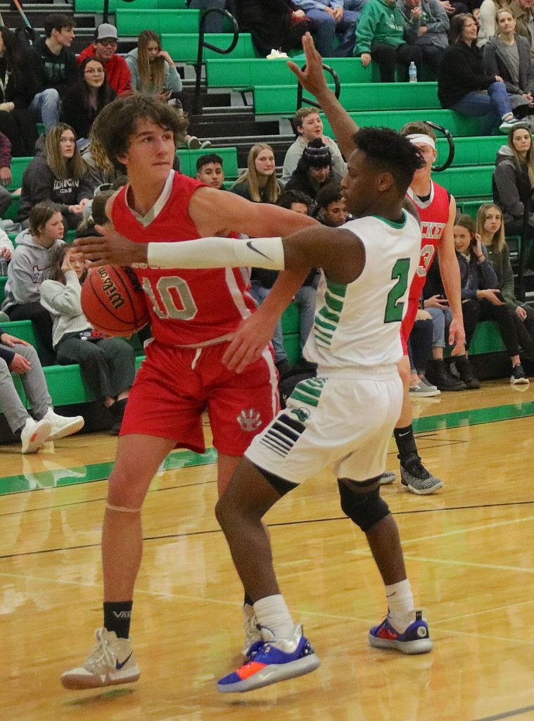 The Greenwave's Elijah Jackson guards Truckee's Sam Purgason.