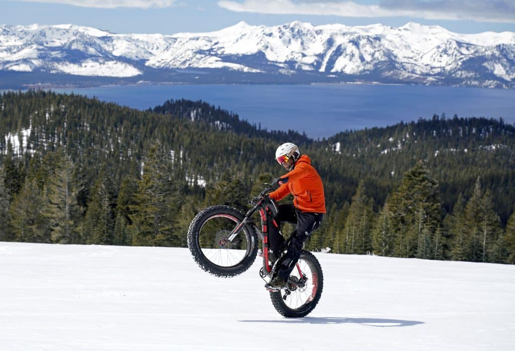 Ian Kirk pops a wheelie while riding a fat bike in the Lake Tahoe region this past winter.