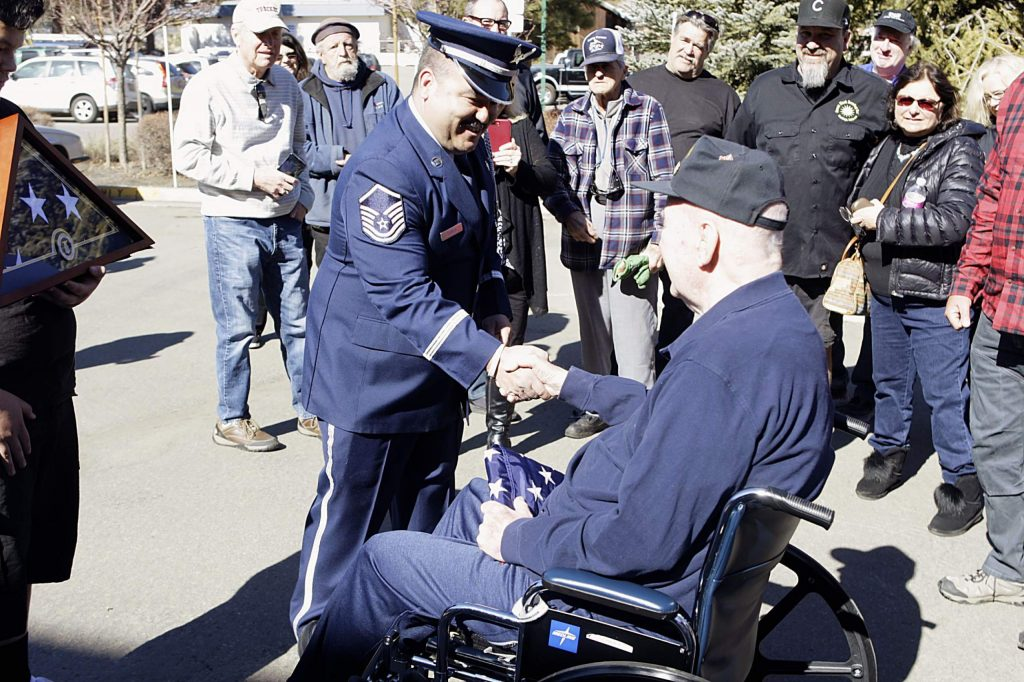 Korean War veteran William J. Brown and Master Sgt. Roberto Fabela shake hands during a ceremony honoring Brown on Saturday, Feb. 22.