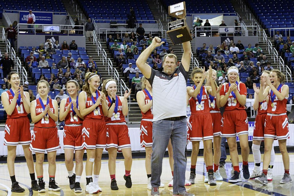 Truckee Coach David Shalvis raises the state championship trophy after the Lady Wolverines defeated Fernley at Lawlor Events Center.