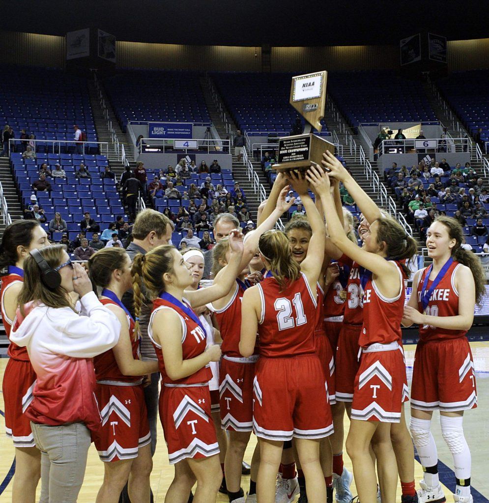 The Truckee girls' basketball team hoists the NIAA state championship trophy for the first time in school history.