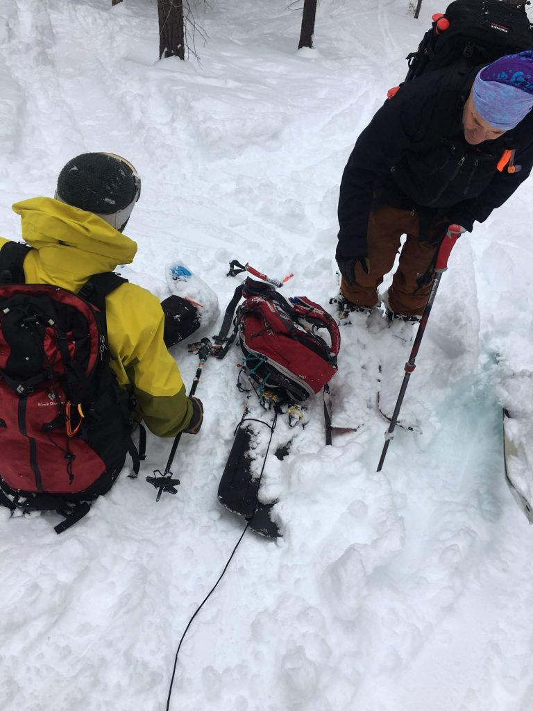 Matt Hedley (lower left) and a friend make a sled from skis and a pole.