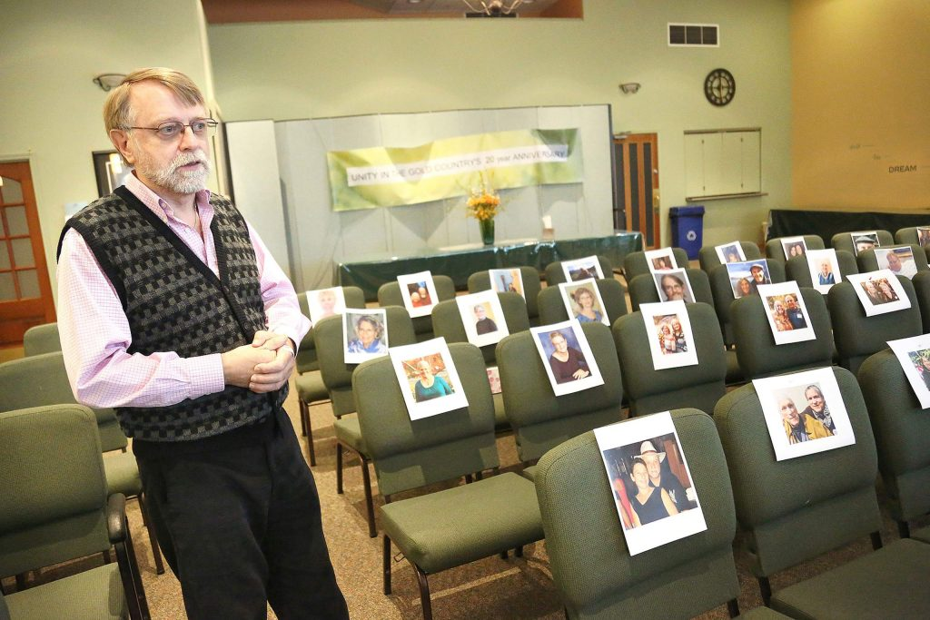 Unity in the Gold Country Spiritual Center's Rev. Jerry Farrell stands among pictures of his congregation, placed on the seats of the Cambridge Court center on March 26. Farrell is using Zoom and FaceTime to connect with people and will be using the sanctuary for a Wall of Remembrance to help those grieving their loved ones during this time.