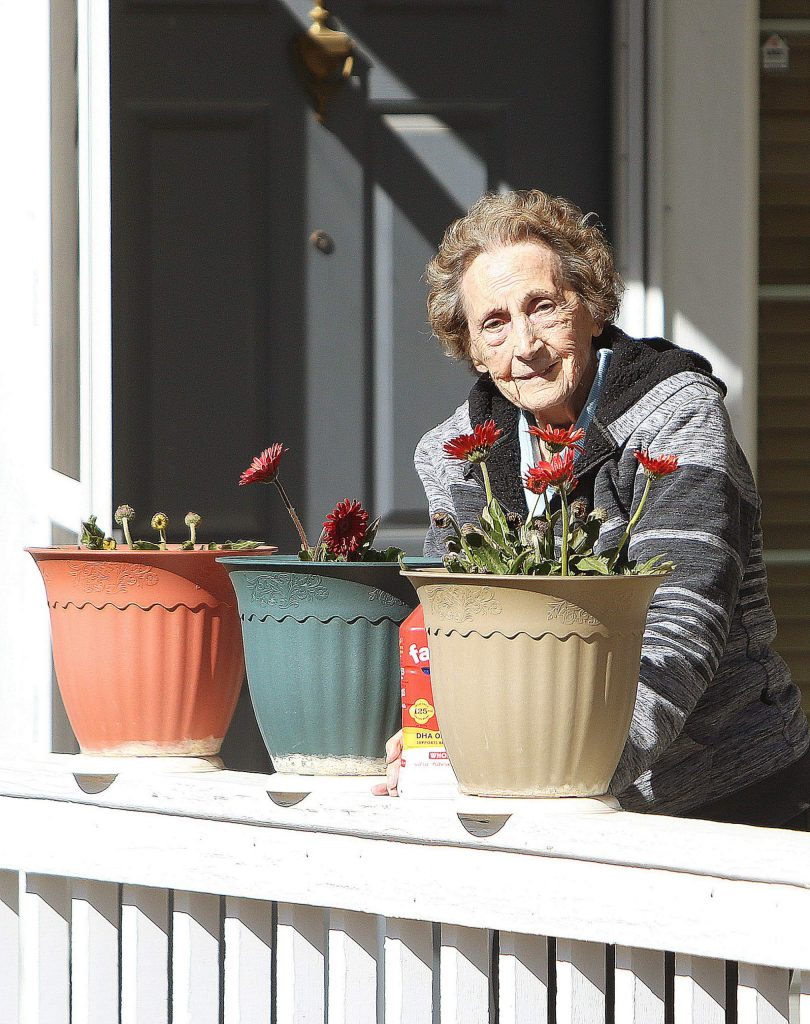 A Sparrow Circle resident waters flowers on her front porch last week in the Eskaton senior living community.