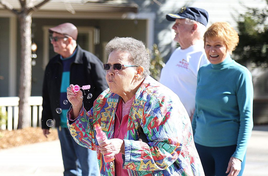 Sparrow Circle resident Priscilla Mayfield demonstrates her bubble blowing technique she uses while making her walks around the neighborhood. Other neighbors use cowbells or dance while on the morning walk.