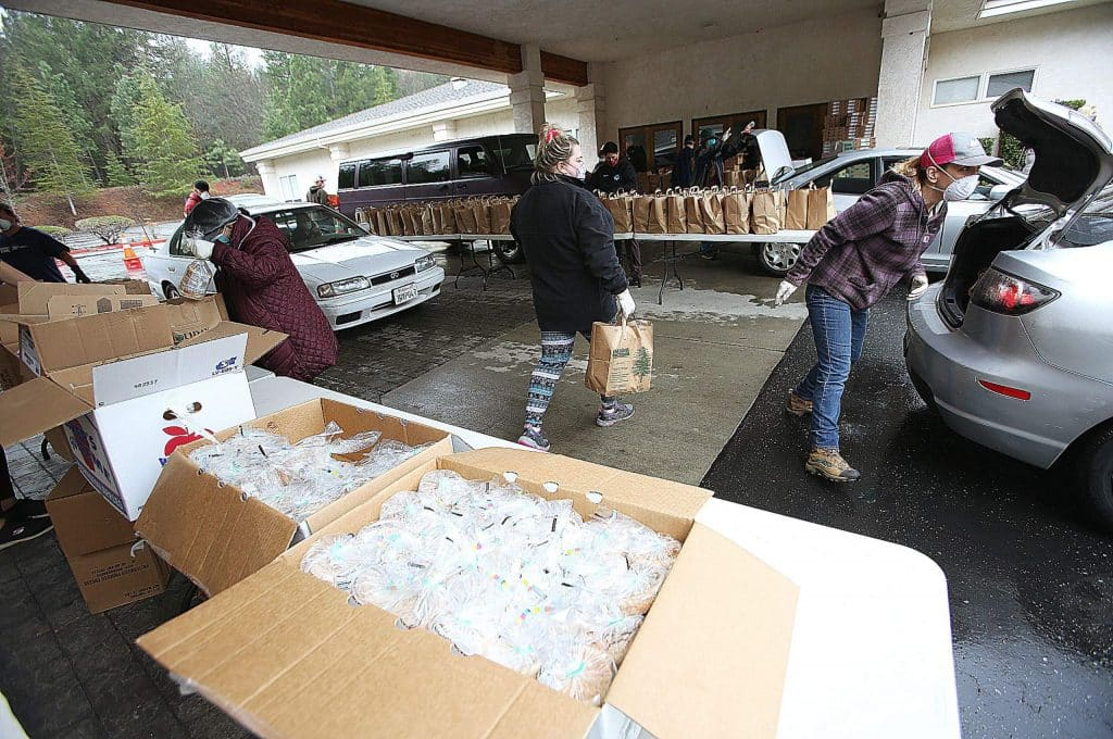 Boxes filled with bags of sliced bread are distributed as vehicles take part in a drive-thru food distribution at the Seventh-day Adventist Church in Grass Valley in late April. The Food Bank of Nevada County has been particularly busy over the last month, as more individuals are in need of reduced price or free food.