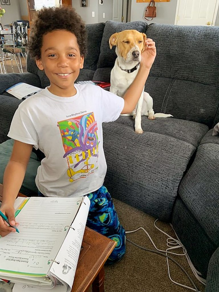 Elijah (a 5th-grader) doing his schoolwork with the help of his BFF Rascal.