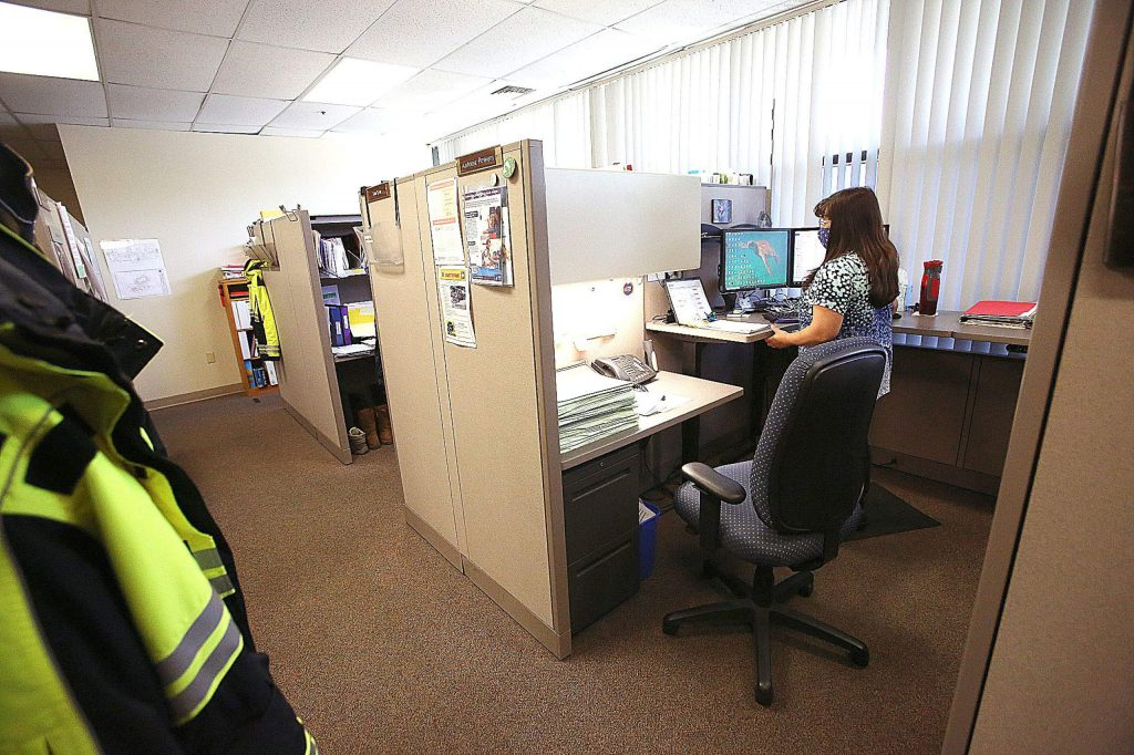 Nevada County's Antonia Powers wears her mask as she works from her cubicle at the Eric Rood Administrative Center last week. Only a handful of county government employees are working in the building while many are working remotely.
