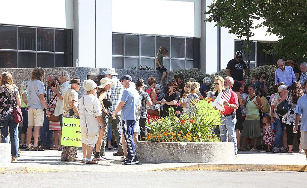 A large gathering of mostly unmasked people met outside the Eric Rood Administrative Center to protest an agenda item that would punish COVID-19 violators. The agenda item was pulled by the Board of Supervisors.