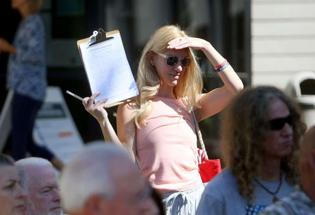 A petition gatherer holds a clipboard for the Nevada County for Empowered Health email list while a group of Free Nevada County protesters stand outside of a closed Eric Rood Administrative Center Tuesday morning in Nevada City.