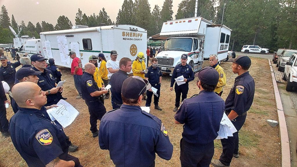 Firefighters get their briefing Wednesday morning at the Eric Rood Administrative Center in Nevada City where an incident command center for the Jones Fire had been established. The fire grew by about 150 acres to over 700 acres on Wednesday.