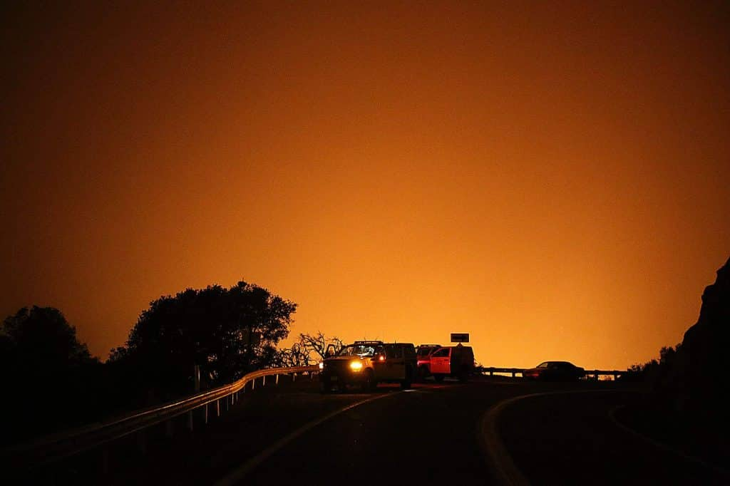 An orange smoke-filled sky from the Jones Fire silhouettes Highway 49 as the fire smolders after burning nearly 500 acres and a handful of homes.