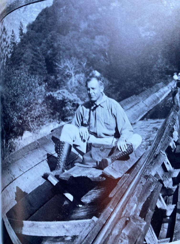 A man rides in a flume boat. V-flumes were used to transport logs, lumber, working material and supplies but they were also used to transport people and for entertainment.